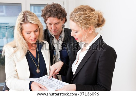 Young realtor explain lease agreement or purchase contract with floor layout to couple in an apartment, close-up - stock photo