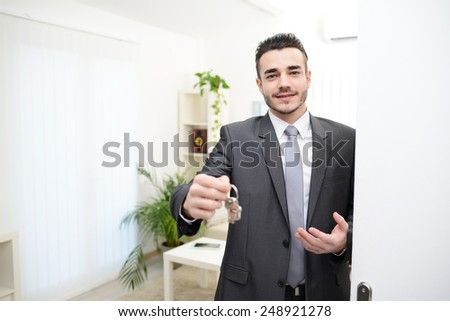 young realtor handing house keys in doorway of new house - stock photo