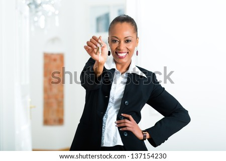 Young realtor with keys in an apartment, it could be the tenant too - stock photo