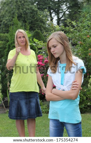 Young rebellious sullen teenage girl in an argument with her mother who is admonishing her with a pointing finger
