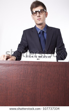 Young receptionist showing direction to exam room. - stock photo