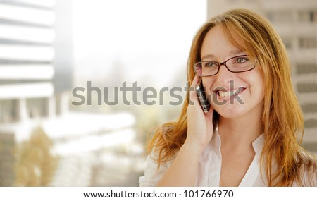 Young red hair business woman is  on the phone and smiling while doing business