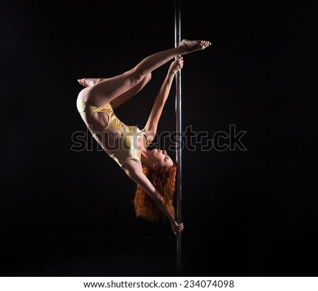 Young red-hair model doing trick on pole. Fitness sport model training inside