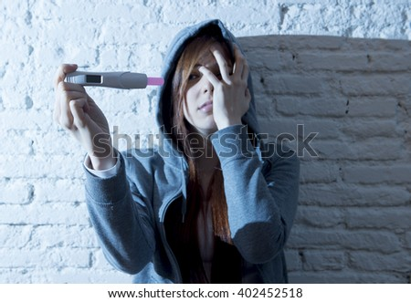 young red hair teenager girl or young woman worried in shock and overwhelmed after positive pregnancy test devastated and depressed in youth unwanted maternity concept - stock photo