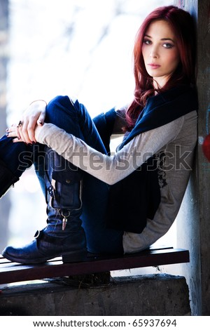 young red hair woman in casual clothes sit on bench, outdoor shot