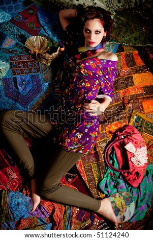 young red hair woman sitting in colorful clothes
