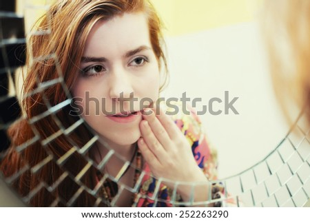 Young red-haired girl doing morning makeup before the mirror - stock photo