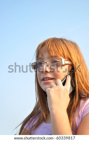 Young, red-haired girl talking on the phone - stock photo