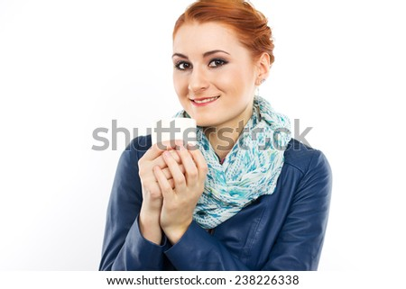 Young red-haired girl with a cup of hot coffee