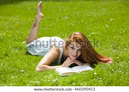 young red haired woman student relaxing learning in park sunny weather summer