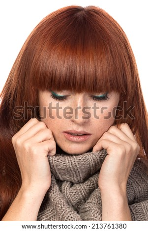Young red-haired woman wrapping herself in warm knitted shawl - stock photo