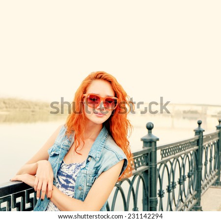 Young red haired women in funny orange sunglasses posing near fence, a lot of copyspace - stock photo