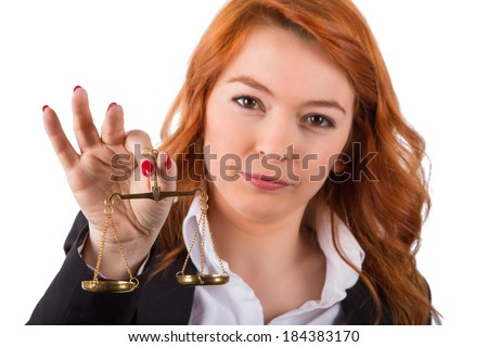 Young red head business woman holding scales, isolated on white background. - stock photo