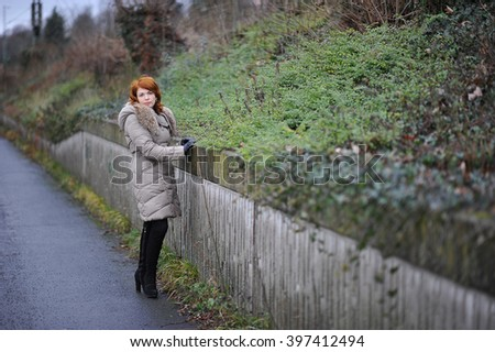 young red-headed girl in a coat with fur and tall black boots stands about the green fence