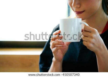 Young red lips woman drinking coffee in a white ceramic cup in vintage tone (selective focus at woman's hand and coffee cup)