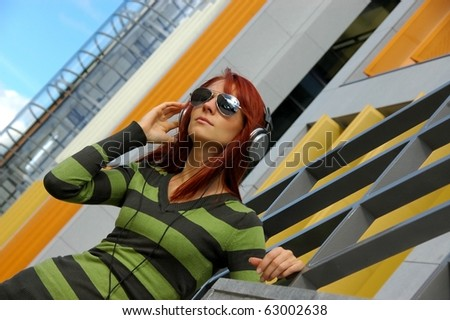 Young red woman enjoying music outdoors - stock photo