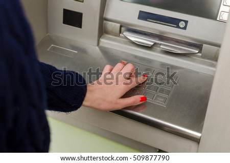 Young red woman using the cash machine on the street