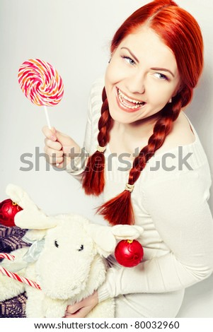 young redhair woman with deer toy. christmas picture.