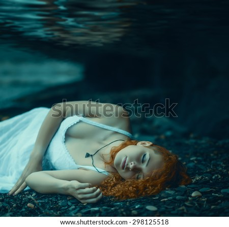 Young redhead beautiful woman lying underwater. - stock photo