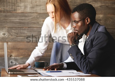 Young redhead Caucasian female secretary showing a report to her young African American boss on laptop computer. Two corporate associates of different races working together on a project at a cafe - stock photo