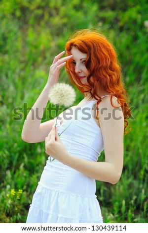 Young redhead female with one big dandelion, outdoor shoot. - stock photo