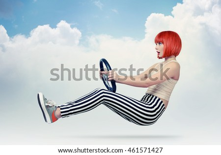 Young redhead girl driver car with a wheel in clouds, auto concept