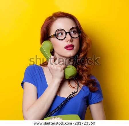 Young redhead girl in blue dress with dial phone on yellow background.
