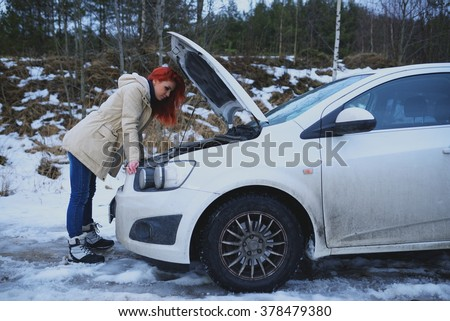Young redhead girl looks under cowl of broken car on rural road - stock photo