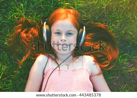 young redhead girl lying in summer grass with headphones listening to music and relaxing - stock photo