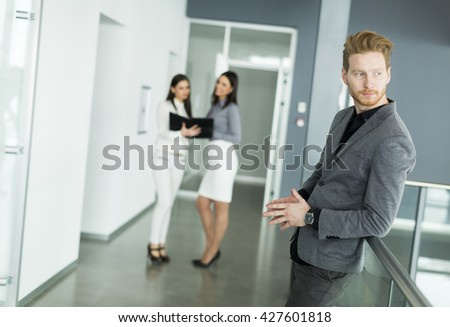 Young redhead man in the office with women colleagues