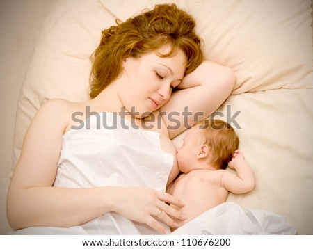 Young redhead mother is breast feeding a newborn baby and dreaming. They are lying on the bed hidden by a sheet. The symbol mother love and happiness - stock photo