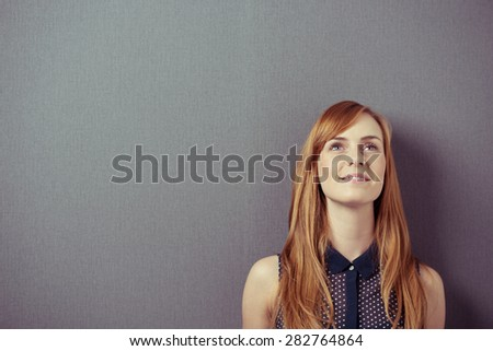 Young redhead pretty woman wearing a sleeveless shirt while smiling and looking up with a positive attitude, planning or anticipating a great future, portrait with copy space on grey - stock photo