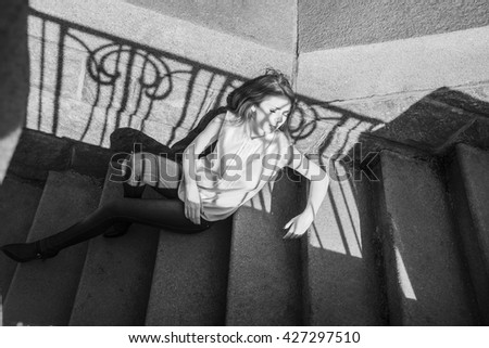 Young redhead teenage relaxed model girl posing on stadium stoned stairs, wearing blue jeans and white shirt. Sad ginger woman sit on sunny light with shadow on face - stock photo