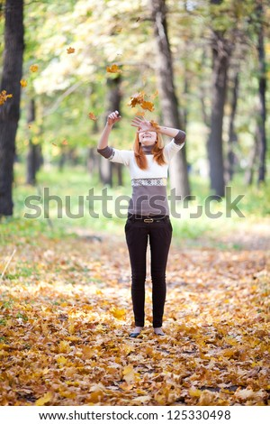 young redhead teenager throwing leaves woman in the forest - stock photo