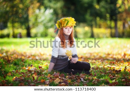 young redhead teenager woman in a wreath of maple leaves sitting on the grass - stock photo