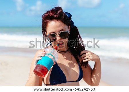 Young redhead woman drinking strawberry cocktail on the beach