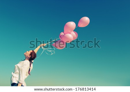 Young redhead woman holding pink balloons - stock photo
