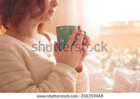 Young redhead woman in cosy sweater drinking hot drink in vinter home - stock photo