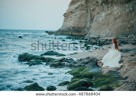 Young redhead woman in white bridal vintage dress at the seaside