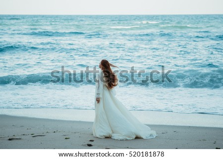 Young redhead woman in white bridal vintage dress walking at the seaside. Meditation