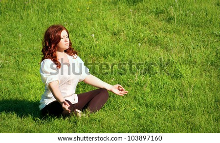 young redhead woman practicing yoga lotus pose outdoors on the grass on the lawn in the park - stock photo