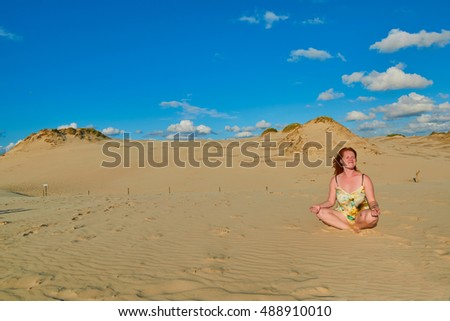 Young redhead woman sitting in relaxed  Yoga Position under the sun among Sand Dunes of Leba, Poland