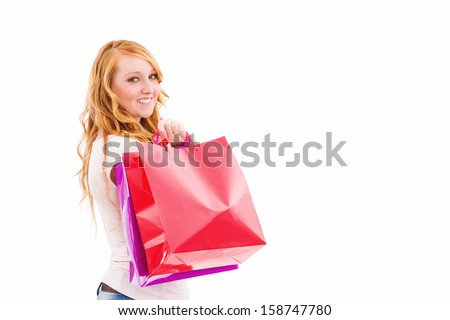 young redhead woman with shopping bags turning around on white background - stock photo