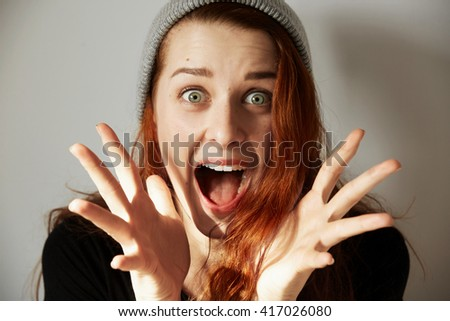 Young redhead woman with surprised expression looking at the camera, screaming with mouth wide open. Female shocked with sale prices while shopping online. Positive human face expressions and emotions