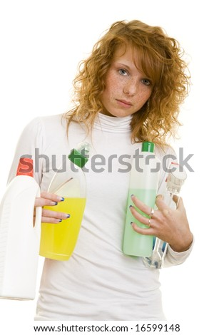 Young redheaded woman holding cleaning supplies - stock photo