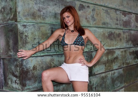 Young redheaded woman in bikini top and white shorts against a rusty green wall
