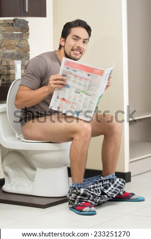 young relaxed hispanic man sitting on the toilet reading the paper - stock photo