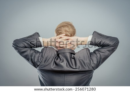 Young relaxed man in hat with hands behind head - stock photo
