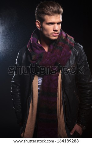 young relaxed man in leather jacket is standing with his hands in his pockets and looks away from the camera - stock photo