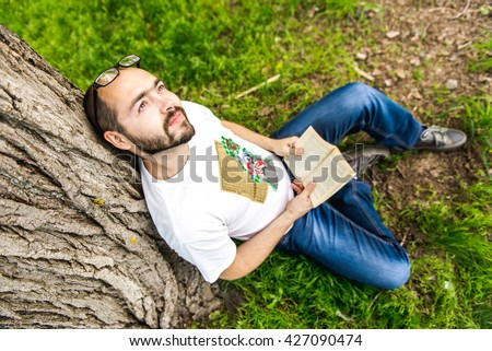 Young relaxed man reading book in nature, back on tree, meadow behind - stock photo